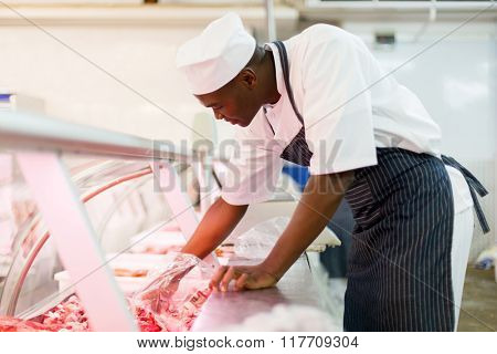 young african american butcher picking pieces of meat  in butchery