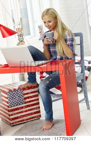 Young woman browsing internet on laptop at home, drinking tea.