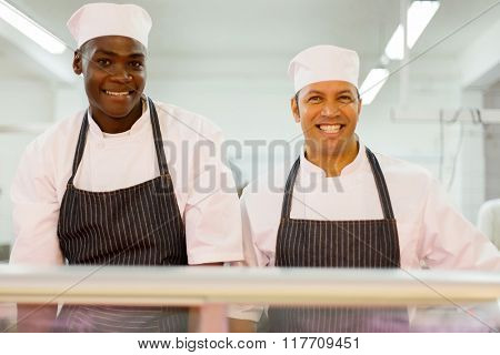 portrait of smiling multiracial butchery co-workers looking at the camera