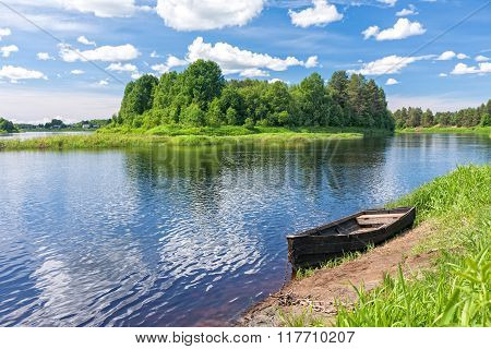 View on river with island and wooden boat laid up on riverbank
