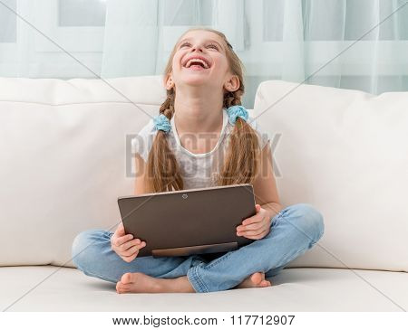 little girl laughs holding notebook on her crossed legs on sofa