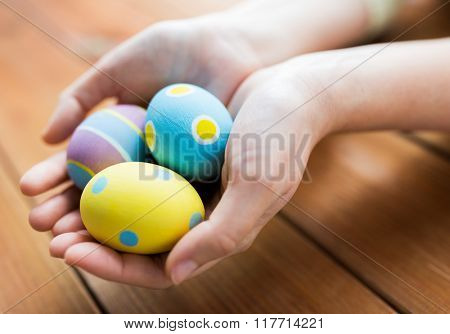 easter, holidays, tradition and people concept - close up of woman hands holding colored easter eggs