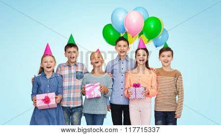 childhood, holidays, friendship and people concept - happy smiling children in party hats with gifts and balloons on birthday over blue background