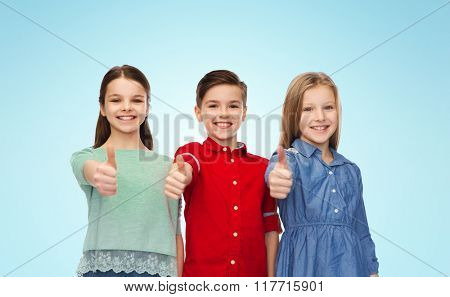 childhood, fashion, gesture and people concept - happy smiling boy and girls showing thumbs up over blue background