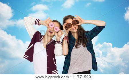people, friends, teens and friendship concept - happy smiling pretty teenage girls with donuts making faces and having fun over blue sky and clouds background