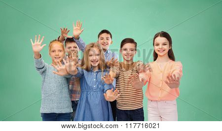 childhood, education, friendship, gesture and people concept - happy smiling children waving hands over green school chalk board background