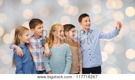 childhood, friendship, technology and people concept - happy children talking selfie by smartphone over holidays lights background