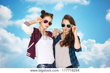 people, friendship, fashion, summer and teens concept - happy smiling pretty teenage girls in sunglasses over blue sky and clouds background