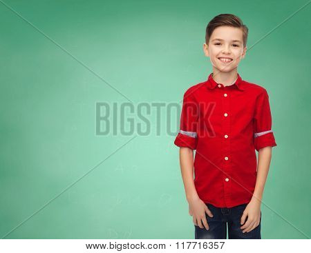 childhood, education, school and people concept - happy smiling boy in red shirt over green chalk board background