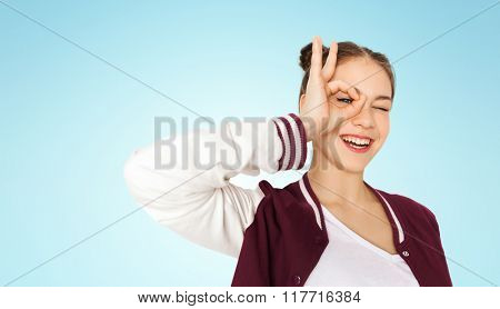 people and teens concept - happy smiling pretty teenage girl making face and having fun over blue background