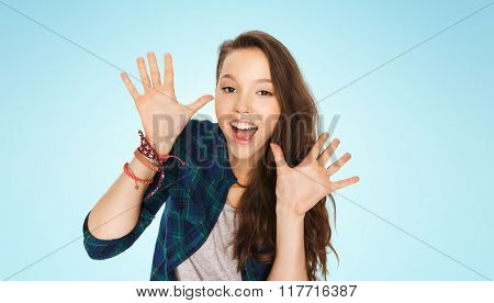 people and teens concept - happy laughing pretty teenage girl showing hands over blue background
