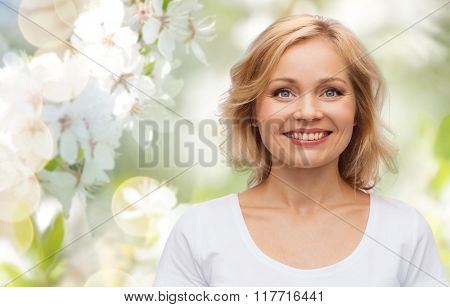 spring, nature and people concept - smiling woman in blank white t-shirt over cherry blossom background