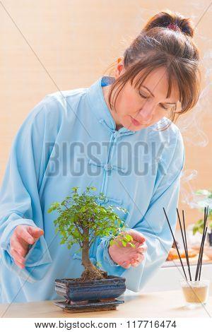 Beautiful woman wearing traditional chinese uniform with bonsai tree