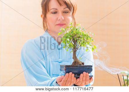 Beautiful woman wearing traditional chinese uniform holding bonsai tree