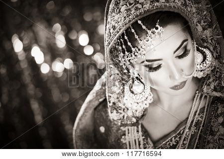 Portrait of a beautiful female fashion model in ethnic asian indian bridal costume with heavy jewellery and makeup