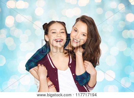 people, friends, teens and friendship concept - happy smiling pretty teenage girls hugging over blue holidays lights background