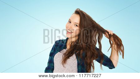 people, hair care, style and teens concept - happy smiling pretty teenage girl holding strand of her hair over blue background