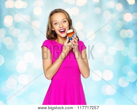 people, holidays, party, junk food and celebration concept - happy young woman or teen girl in pink dress with cupcake over blue holidays lights background