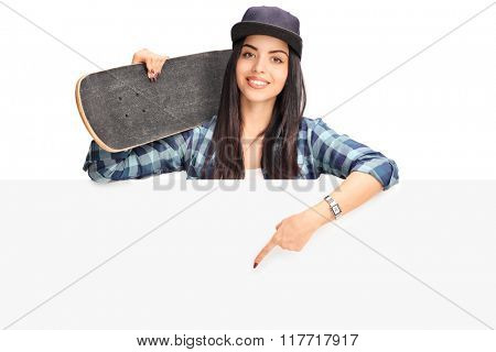 Studio shot of a skater girl holding a skateboard and pointing on a blank signboard isolated on white background