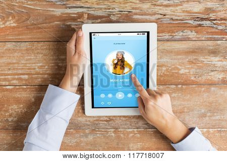 media, entertainment, people and technology concept - close up of female hands pointing finger to tablet pc computer with music player on screen