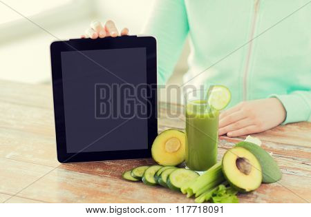 healthy eating, technology, diet and people concept - close up of woman hands with tablet pc, green fresh juice and vegetables sitting at table