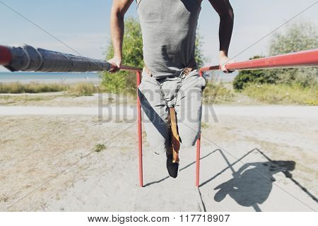 fitness, sport, exercising, training and lifestyle concept - close up of young man doing triceps dip with weight belt on parallel bars outdoors