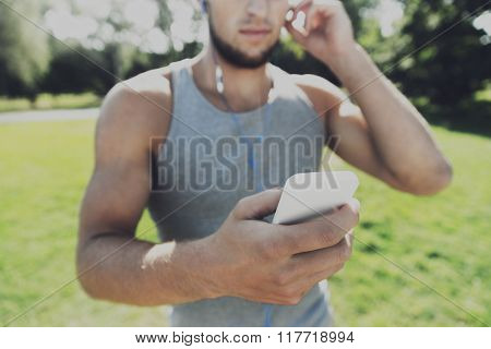 fitness, sport, technology and lifestyle concept - close up of young man with smartphone and earphones listening to music at summer park