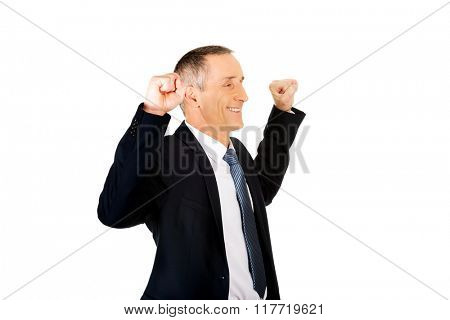 Portrait of successful businessman with arms up