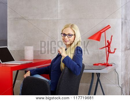 Beautiful young blonde woman sitting at desk, working with laptop computer, smiling at camera.