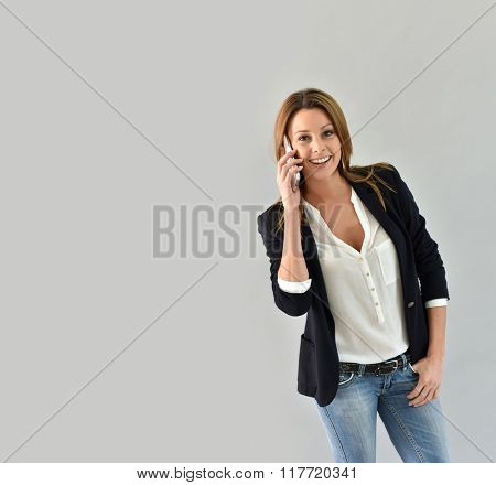 Beautiful trendy woman using smartphone, grey background