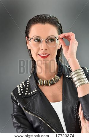 Beautiful trendy woman with eyeglasses, grey background