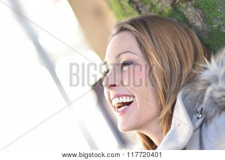 Profile view of young woman laughing outloud