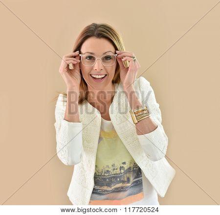 Trendy girl with eyeglasses, beige background