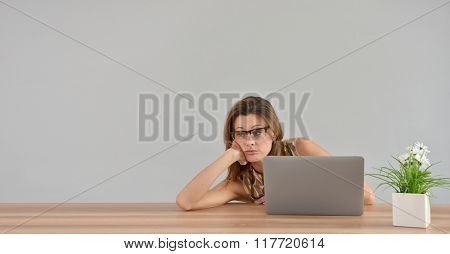 Woman in front of laptop with boring look, isolated