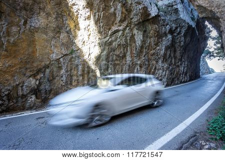 Asphalt road between rocks with blurred white car