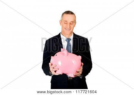 Portrait of cheerful businessman holding piggybank