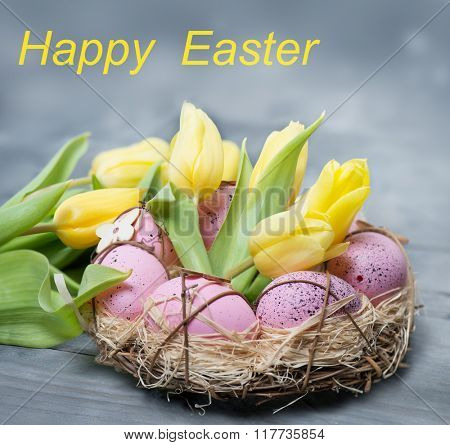 Pink Easter eggs lying in a nest along with spring yellow tulips