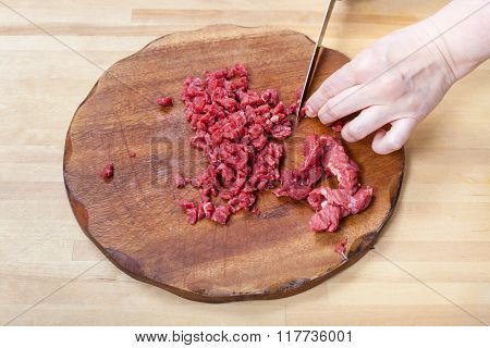 Woman Cuts Meat On Wooden Cutting Board