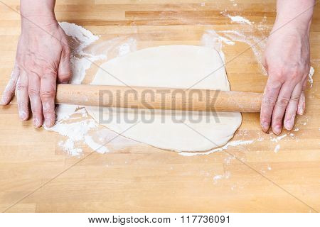 Female Hands Roll Out Dough With Rolling Pin