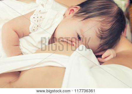 Soft focus image of newborn baby breastfeeding