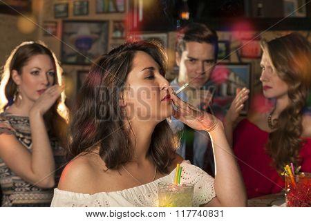 Friends make derogatory gestures to smoking of their friend