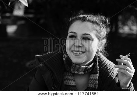 Young beautiful woman smoker in a park, outdoors
