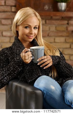 Attractive young blonde woman sitting in armchair at home, drinking tea, smiling, looking at camera.