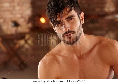 Closeup photo of sexy latin man with bare chest, looking at camera.