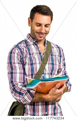 Smiling man standing with notepads on white screen