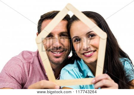 Young couple holding house shape on white screen