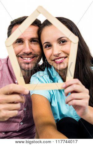 Couple holding house shape on white screen