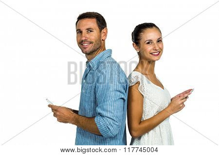 Smiling couple standing back to back using smartphones on white screen