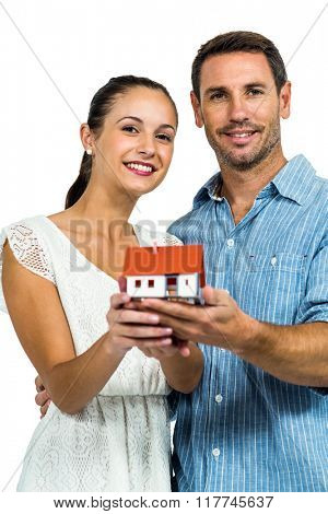 Confident couple holding house model on white screen