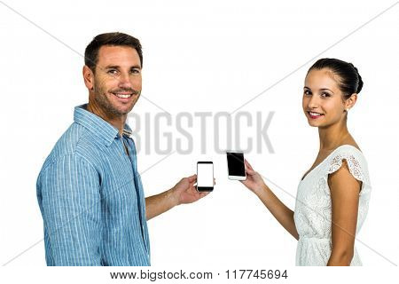 Smiling couple holding smartphones and looking back at camera on white screen